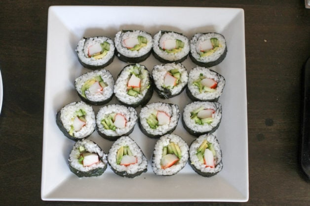 Homemade sushi on a square white plate.