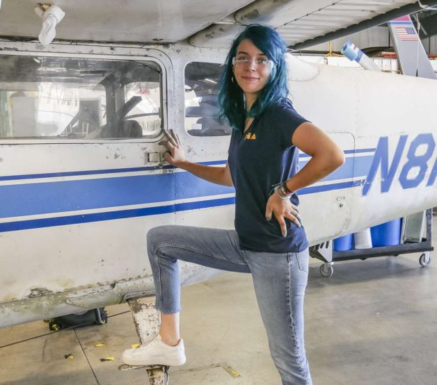 Lisey standing next to a small airplane.