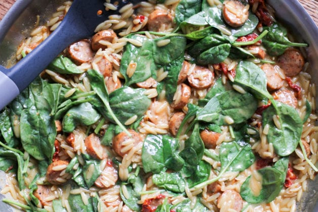 Orzo and spinach in a pan.