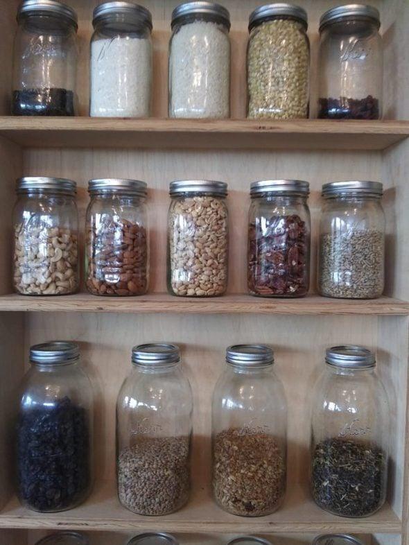 A pantry shelf full of glass jars.