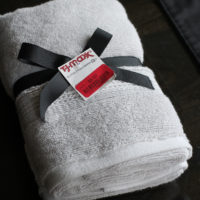 Gray hand towels tied with a black ribbon.