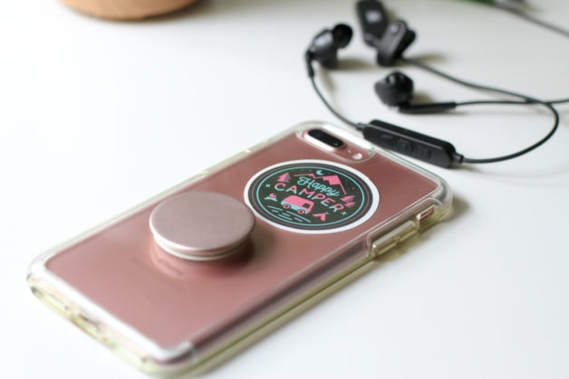 A pink iphone with a happy camper sticker on the back.