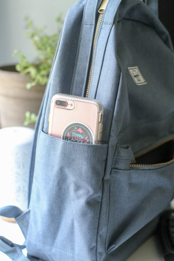 A pink phone in a blue backpack pocket.