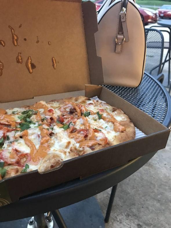 Panera chipotle pizza in a cardboard box.