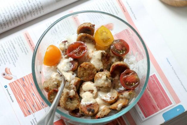 A bowl of rice, sausage, and veggies.