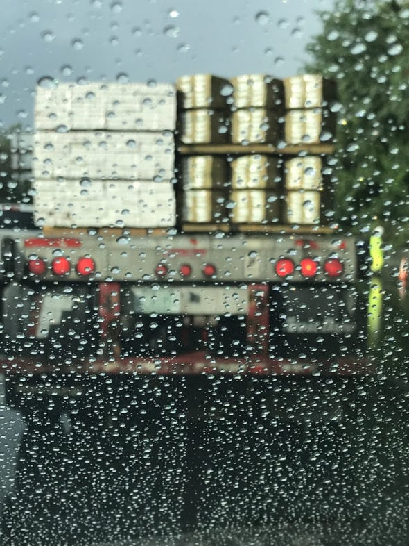 A view of a truck through a rainy windshield.
