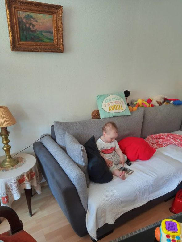 A little boy sitting on a couch.