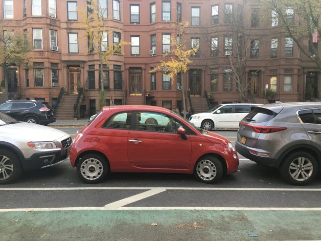 A red fiat parked in New York City.