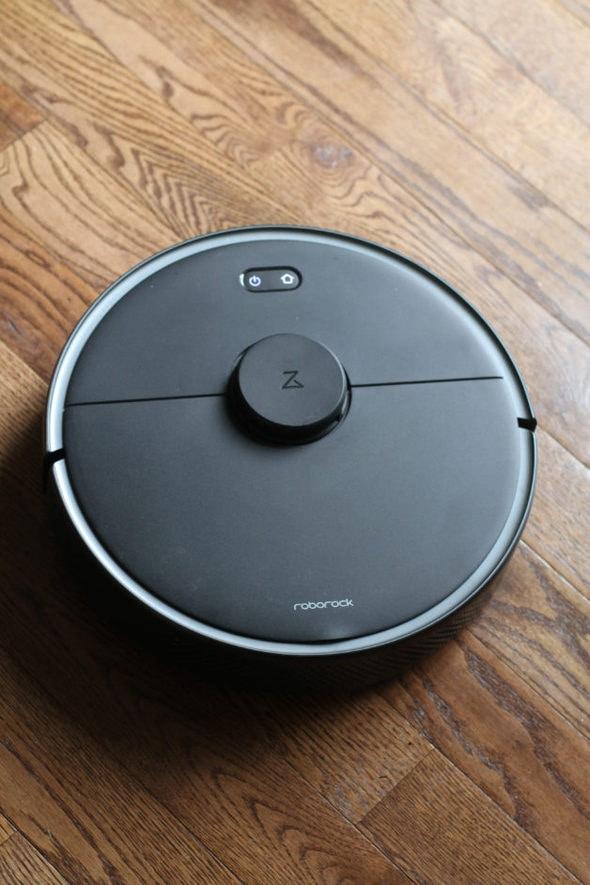 Black vacuum on a brown wood floor.
