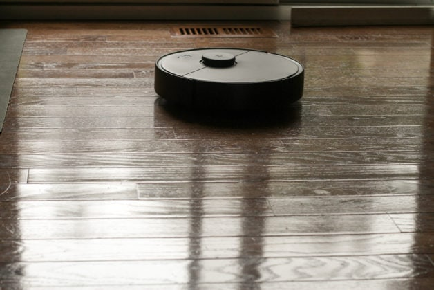 A black robot vacuum on a wood floor.