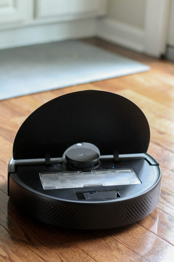 A Roborock vacuum with the lid up.
